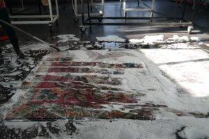 Eingeseiften Teppich schrubben